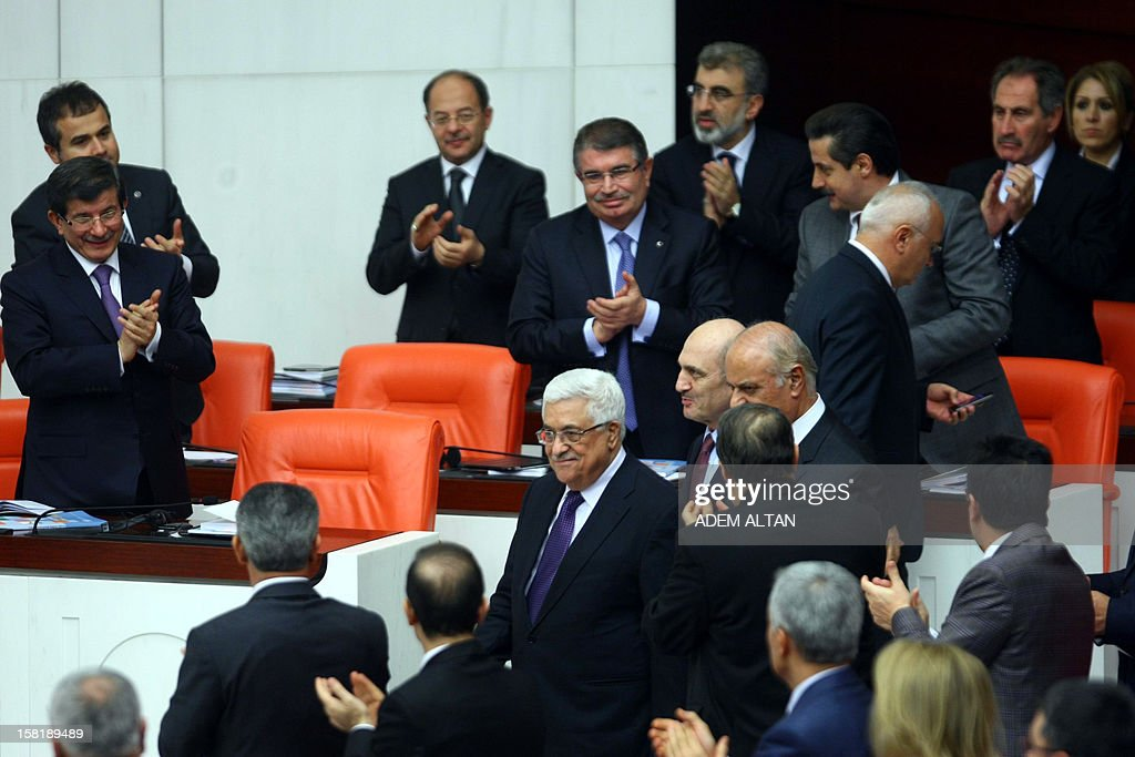 Palestinian president Mahmud Abbas (C) is greeted by Turkish lawmakers upon his arrival before delivering a speech at the Turkish Parliament, on December 10, 2012 in Ankara. The UN General Assembly overwhelmingly backed a resolution to recognise Palestine as a non-member observer state, a move Abbas said on December 5, 2012 was part of 'a last chance' for a negotiated two-state solution. Turkey welcomed the upgrading of the Palestinians' status as a 'significant step', with Foreign Minister Ahmet Davutoglu calling for an independent Palestinian state with east Jerusalem as its capital. In background, at right, Turkish Prime Minister Recep Tayyip Erdogan.