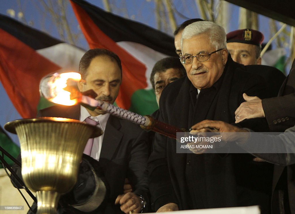 Palestinian President Mahmud Abbas lights a flame as thousands of Palestinians look on, on the eve of the 48th anniversary of the formation on the Fatah movement, on December 31, 2012, in the West Bank city of Ramallah. The Fatah anniversary commemorates the first operation against Israel claimed by its armed wing then known as Al-Assifa (The Thunderstorm in Arabic) on January 1, 1965.