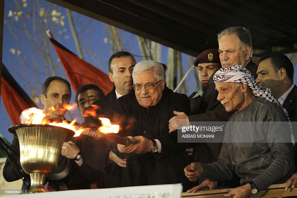 Palestinian President Mahmud Abbas lights a torch following his speech in front of thousands of Palestinians on the eve of the 48th anniversary of the formation on the Fatah movement, on December 31, 2012, in the West Bank city of Ramallah. The Fatah anniversary commemorates the first operation against Israel claimed by its armed wing then known as Al-Assifa (The Thunderstorm in Arabic) on January 1, 1965. AFP PHOTO/ABBAS MOMANI