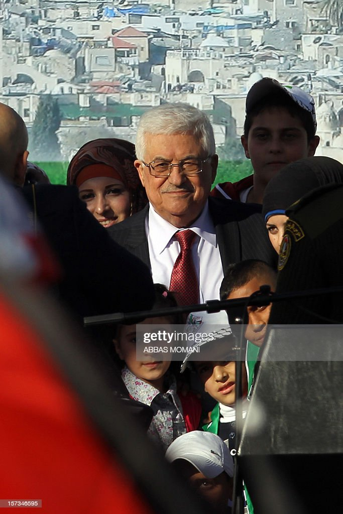 Palestinian president Mahmud Abbas (C) poses for a photo after delivering a speech to cheering crowds upon his arrival in the West Bank city of Ramallah on December 2, 2012. Abbas said 'Palestine has accomplished a historic achievement at the UN,' three days after the United Nations General Assembly granted the Palestinians non-member state observer status in a 138-9 vote.