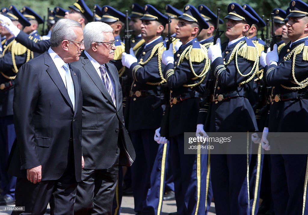 Palestinian president Mahmud Abbas (R) review the guard of honour with Lebanese President Michel Sleiman (L) at the presidential palace of Baabda on July 3, 2013. Abbas flew to Lebanon via Jordan, and is expected to offer the Lebanese authorities assurances that the Palestinian refugee camps will stay clear of the country's growing Syria-related unrest during his three day visit. AFP PHOTO PHOTO/JOSEPH EID