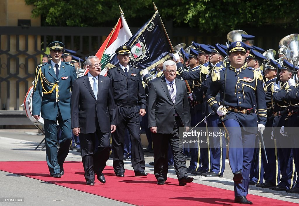 Palestinian president Mahmud Abbas (R) reviews the guard of honour with Lebanese President Michel Sleiman (L) at the presidential palace of Baabda on July 3, 2013. Abbas flew to Lebanon via Jordan, and is expected to offer the Lebanese authorities assurances that the Palestinian refugee camps will stay clear of the country's growing Syria-related unrest during his three day visit. AFP PHOTO PHOTO/JOSEPH EID