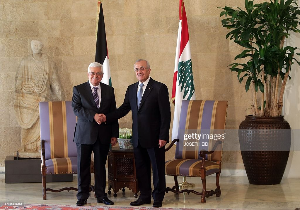 Palestinian president Mahmud Abbas shakes hands with Lebanese President Michel Sleiman (R) at the presidential palace of Baabda on July 3, 2013. Abbas flew to Lebanon via Jordan, and is expected to offer the Lebanese authorities assurances that the Palestinian refugee camps will stay clear of the country's growing Syria-related unrest during his three day visit. AFP PHOTO PHOTO/JOSEPH EID