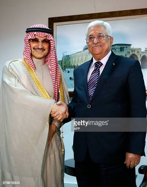 Palestinian President Mahmud Abbas shakes hands with Saudi Arabia's prince AlWaleed bin Talal during their meeting in the West Bank city of Ramallah...