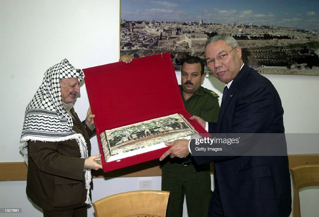 Palestinian President Yasser Arafat, left, presents an official gift June 28, 2001 to U.S. Secretary of State Colin Powell during talks in the West Bank town of Ramallah. Powell told Israeli and Palestinian leaders to seize the chance to end nine months of bloodshed offered by a shaky cease-fire and a U.S.-led plan to resume peacemaking.