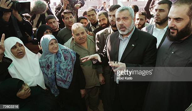 Palestinian Prime Minister Ismail Haniyeh and Hamas leader Sheikh Nezar Rayean visit Palestinian women as they barricade themselves on the roof of a...