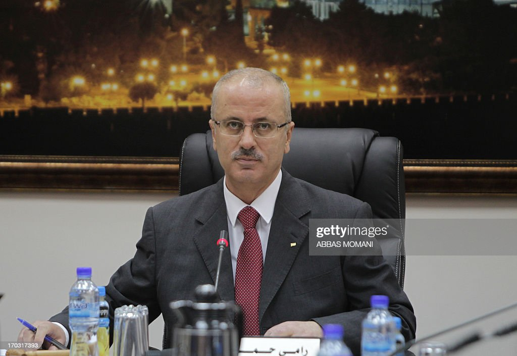 Palestinian Prime Minister Rami Hamdallah chairs the first working meeting of the new Palestinian government in the West Bank town of Ramallah on June 11, 2013. The new government was sworn in on June 6, after the resignation of premier Salam Fayyad in April.