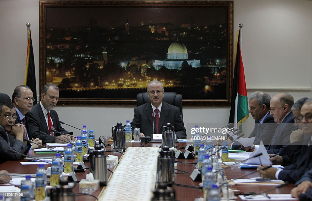 Palestinian Prime Minister Rami Hamdallah (C) chairs the first working meeting of the new Palestinian government in the West Bank town of Ramallah on June 11, 2013. The new government was sworn in on June 6, after the resignation of premier Salam Fayyad in April.