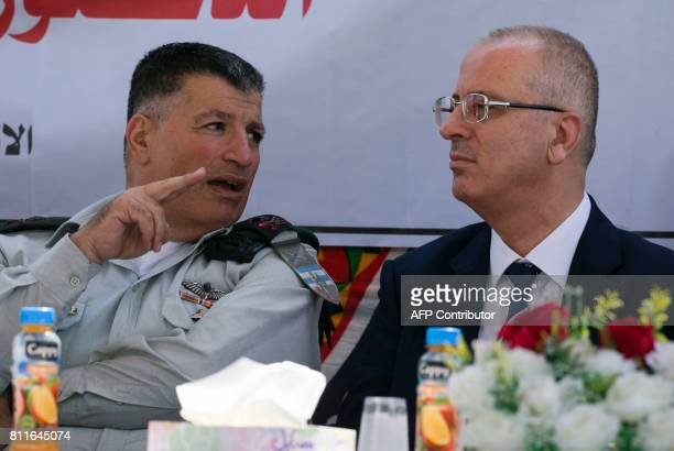 Palestinian prime minister Rami Hamdallah sits next to Major General Yoav Mordechai head of COGAT the Israeli defence ministry agency responsible for...
