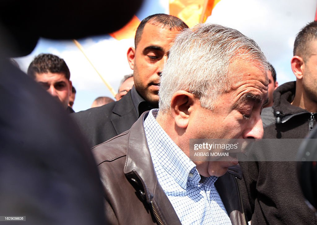 Palestinian Prime Minister Salam Fayyad closes his eye after being caught in tear gas fired by Israeli forces during clashes between hundreds of youths and Israeli security in the West Bank village of Bilin on March 1, 2013, following a large march which headed towards Israel's controversial separation barrier in support of Palestinian prisoners held in Israeli jails, and marking eight years of weekly protests which kicked off in February 2005, against Israel's barrier which encroaches on Palestinian villagers' lands. AFP PHOTO/ABBAS MOMANI