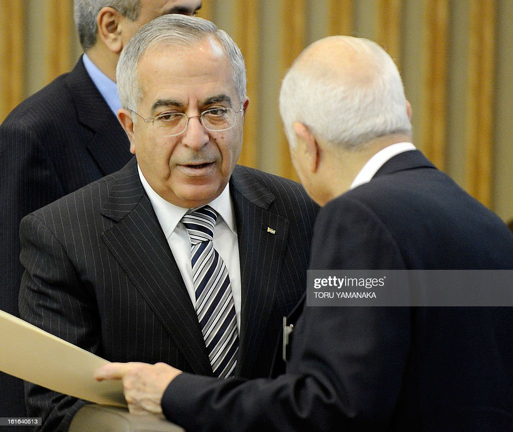 Palestinian Prime Minister Salam Fayyad (L) greets with a representative before the plenary session of the Conference on Cooperation among East Asian Countries for Palestinian Development (CEAPAD) in Tokyo on February 14, 2013. Japan hosted the meeting of Asian countires to discuss financial assistance for the Palestinian Territories. AFP PHOTO/Toru YAMANAKA