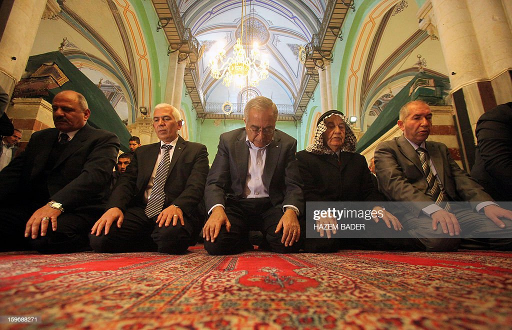 Palestinian prime minister Salam Fayyad (C) prays at Ibrahimi Mosque or the Tomb of the Patriarch in the West bank town of Hebron on January 18, 2013. The Palestinians are bracing for a new right-wing government that Israel's election is expected to produce, hoping that international and domestic moves will strengthen their position. AFP PHOTO / HAZEM BADER