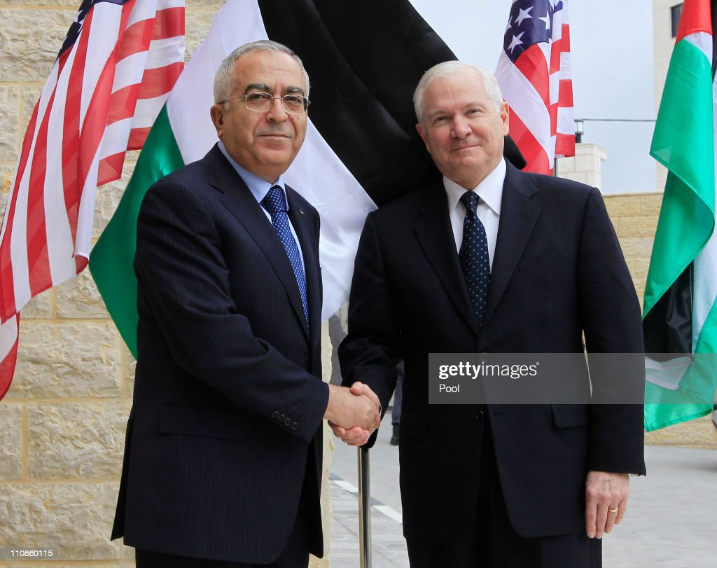 Palestinian Prime Minister <a gi-track='captionPersonalityLinkClicked' href=/galleries/search?phrase=Salam+Fayyad&family=editorial&specificpeople=2162597 ng-click='$event.stopPropagation()'>Salam Fayyad</a> (L) shakes hands with visiting US Defense Secretary Robert Gates on March 25, 2011 in Ramallah, West Bank. As part of his official to the Middle East, US Defense Secretary Robert Gates arrived in the West Bank two days after a bomb explosion at a bus stop in central Jerusalem killed one woman and injured over 20 people, followed by Israeli strikes against Hamas in the Gaza Strip. The first trip to the West Bank city of Ramallah by a US defense chief, Gates is expected to discuss a two-state solution for peace between the Palestinians and Israelis.