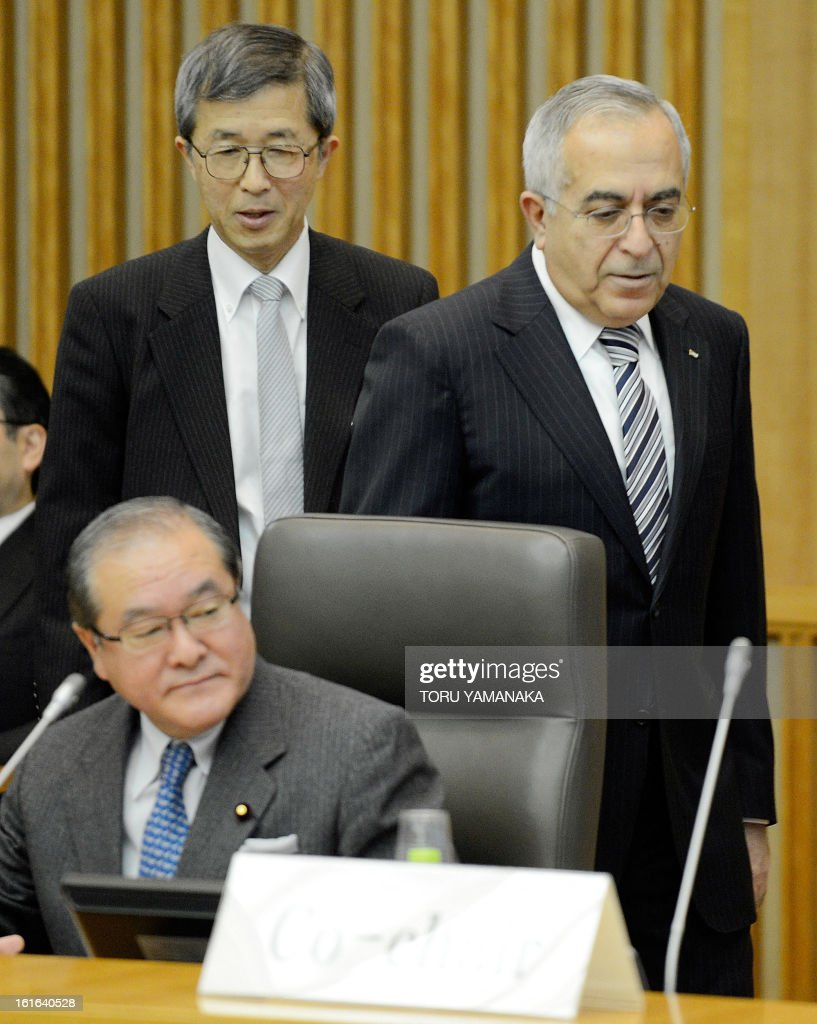 Palestinian Prime Minister Salam Fayyad (R) walks beside Japan's Foreign State Secretary Shunichi Suzuki (L/sitting) and Japan's government special envoy for the Middle East Yutaka Iimura (L/standing) to attend at the plenary session of the Conference on Cooperation among East Asian Countries for Palestinian Development (CEAPAD) in Tokyo on February 14, 2013. Japan hosted the meeting of Asian countires to discuss financial assistance for the Palestinian Territories. AFP PHOTO/Toru YAMANAKA