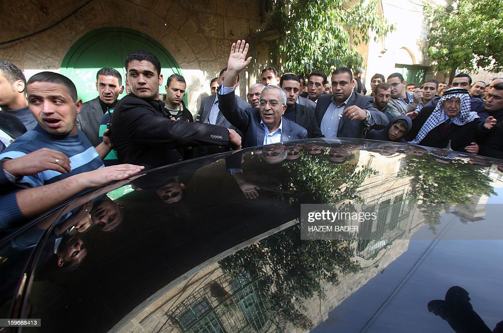 Palestinian prime minister Salam Fayyad (C) waves to supporters as he gets into a car outside Ibrahimi Mosque or the Tomb of the Patriarch following Friday prayers in the West bank town of Hebron on January 18, 2013. The Palestinians are bracing for a new right-wing government that Israel's election is expected to produce, hoping that international and domestic moves will strengthen their position. AFP PHOTO / HAZEM BADER
