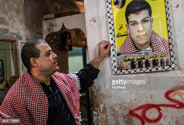 Palestinian prisoner Amr Masoud following his release from an Israeli jail poses for a photo next to a poster of himself at his family's house in...