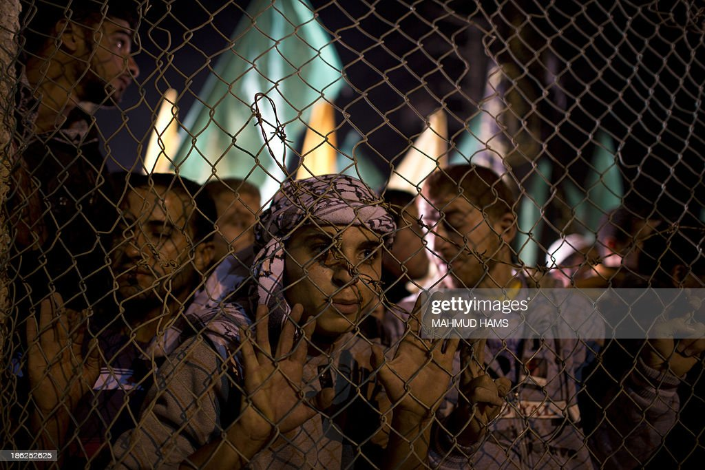 Palestinian prisoners' relatives wait behind a fence for their release at Erez point in the northern Gaza Strip on October 29, 2013. Israel freed 26 veteran Palestinian prisoners early on October 30, 2013 in line with commitments to the US-backed peace process, but moved in tandem to ramp up settlement in annexed east Jerusalem AFP PHOTO / MAHMUD HAMS