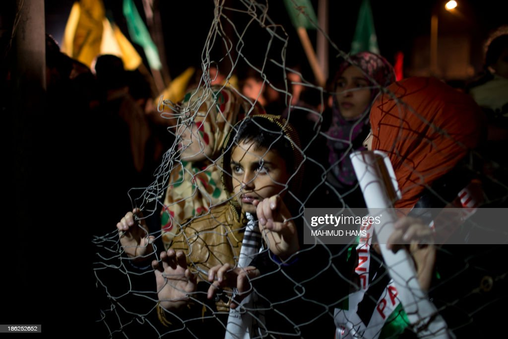 Palestinian prisoners' relatives wait behind a fence for their release at Erez point in the northern Gaza Strip on October 29, 2013. Israel freed 26 veteran Palestinian prisoners early on October 30, 2013 in line with commitments to the US-backed peace process, but moved in tandem to ramp up settlement in annexed east Jerusalem.