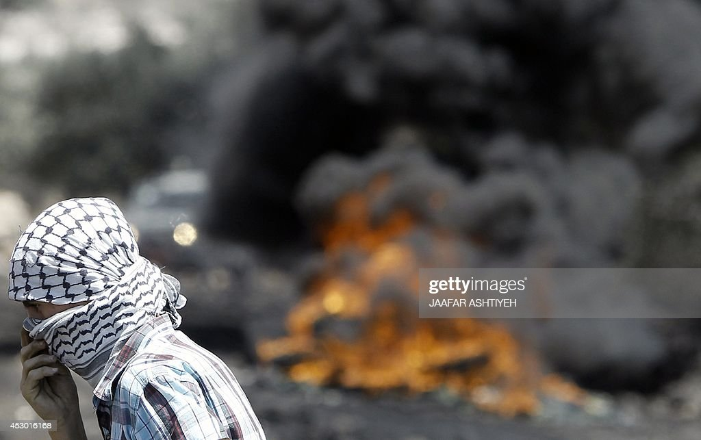 A Palestinian protester adjusts his headscarf as tires burn behind him during clashes with Israeli security forces following a protest in the village of Kfar Qaddum, near the northern city of Nablus, in the occupied West Bank on August 1, 2014. A joint Palestinian delegation, including Hamas and Islamic Jihad, is to travel to Cairo on August 2, for ceasefire talks despite the renewed fighting in Gaza, president Mahmud Abbas's office announced. AFP PHOTO/ JAAFAR ASHTIYEH