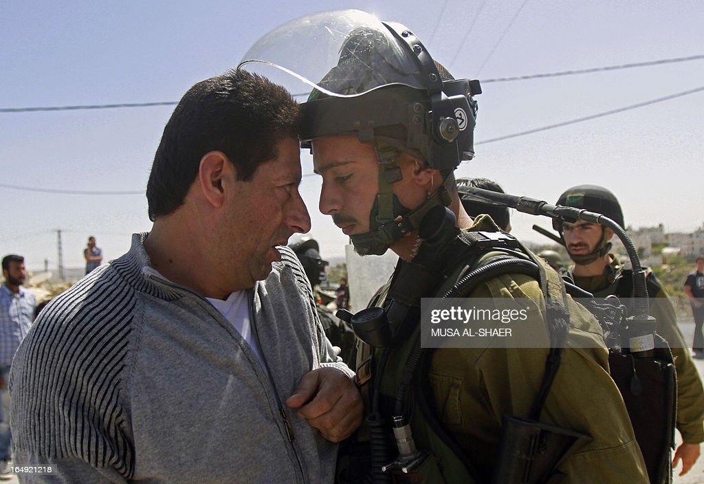 A Palestinian protester argues with an Israeli soldier during a weekly demonstration against the Israeli separation barrier and the expansion of Jewish settlements, in the West Bank village of Maasarah, near Bethlehem, on March 29, 2013. Israel deployed significant security reinforcements in the occupied West Bank including east Jerusalem for demonstrations commemorating the deaths in 1976 of Arab Israelis on 'Land Day'.