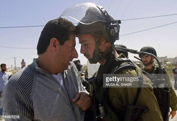A Palestinian protester argues with an Israeli soldier during a weekly demonstration against the Israeli separation barrier and the expansion of...