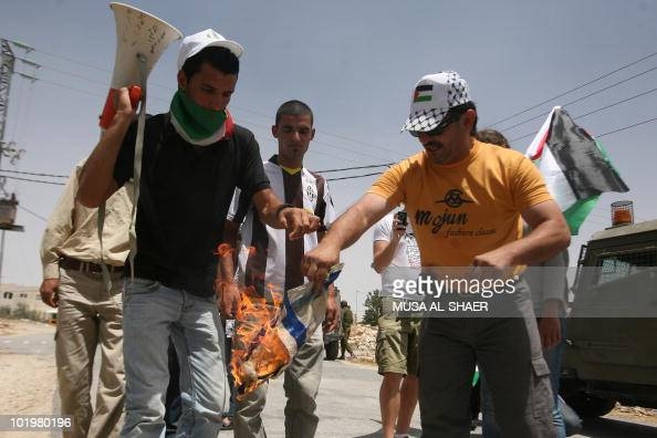 A Palestinian protester burns the Israeli flag during a demonstration by Palestinian Israeli and foreign peace activists against Israel's...