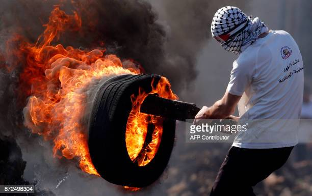 Palestinian protester carries a burning tire during clashes with Israeli forces following a weekly demonstration against the expropriation of...