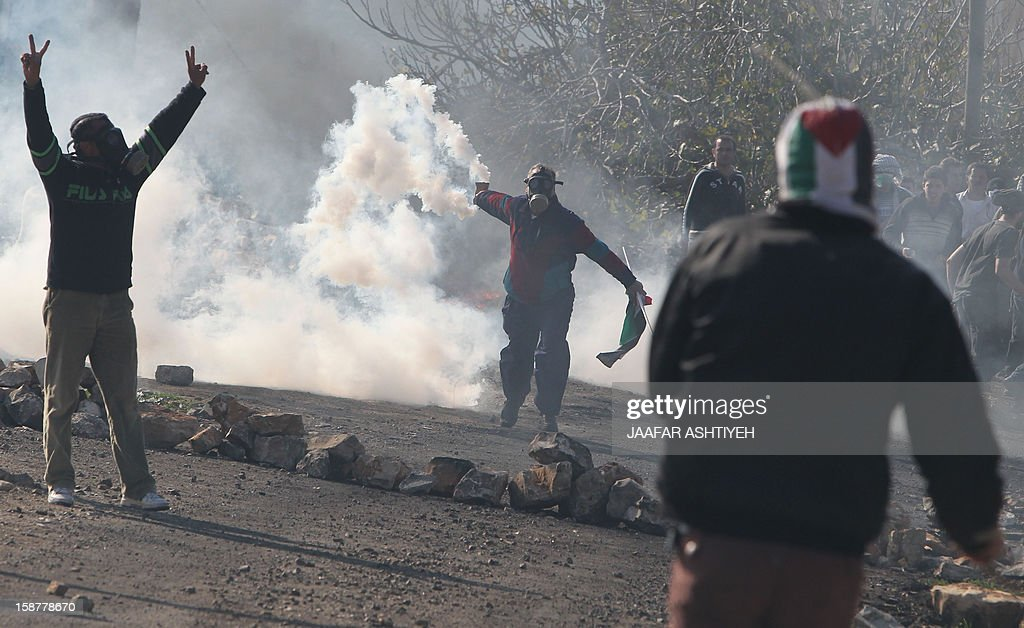 A Palestinian protester carries a tear gas canister fired by Israeli soldiers during clashes following a demonstration against the expropriation of Palestinian land by Israel in the village of Kfar Qaddum, near the occupied West Bank city of Nablus, on December 28, 2012.
