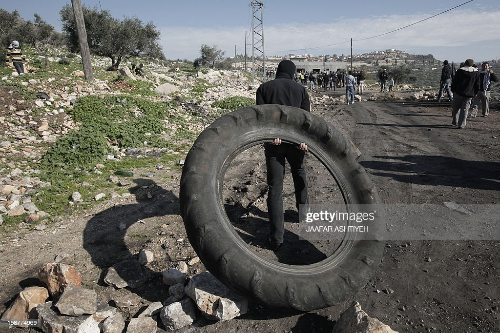 A Palestinian protester carries a tire before burning it during clashes with Isareli soldiers following a demonstration against the expropriation of Palestinian land by Israel in the village of Kfar Qaddum, near the occupied West Bank city of Nablus, on December 28, 2012.