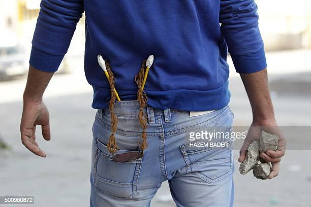 A Palestinian protester carries stones and a slingshot during clashes with Israeli security forces at the northern entrance of the West Bank city of...
