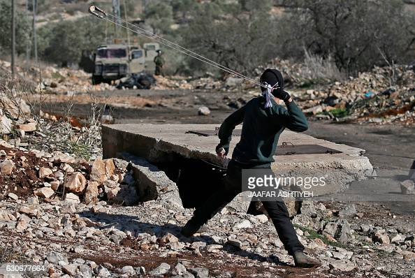 A Palestinian protester clashes with Israeli security forces following a demonstration against the expropriation of Palestinian land by Israel in the...