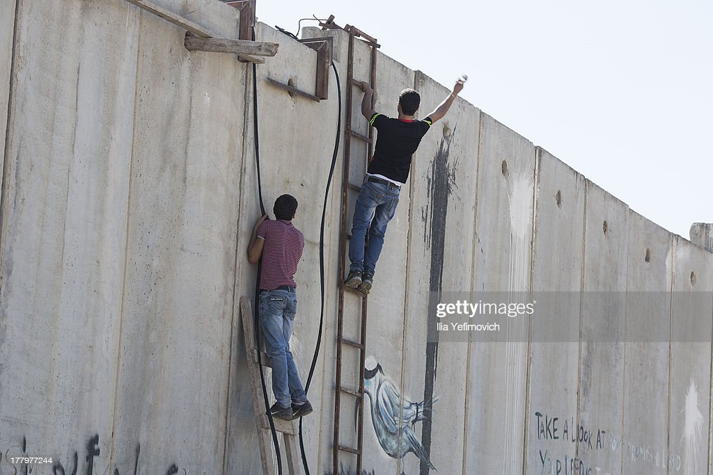 Palestinian protester climb a Israeli separation wall during clashes with IDF after the funeral held for three Palestinians killed during IDF operation at Kalandia refugee camp on August 26, 2013 in Ramallah, West Bank.