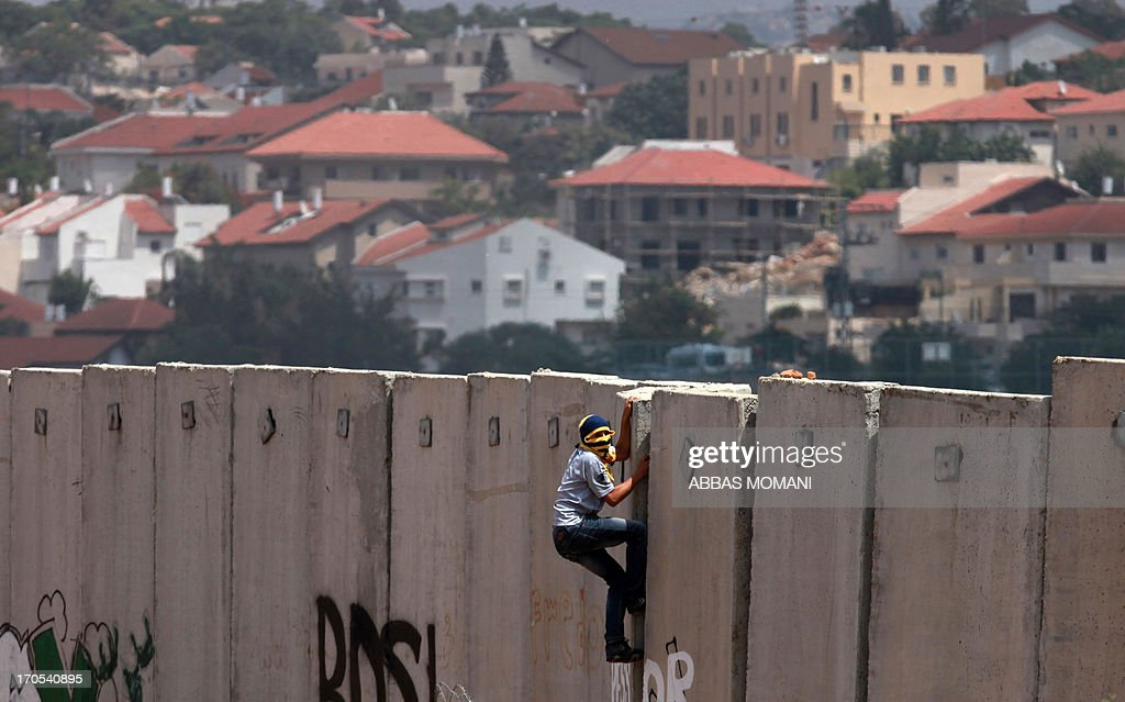 A Palestinian protester climbs Israel's controversial separation barrier during clashes with Israeli security forces following a demonstration against Israeli settlements and its separation wall, in the West Bank village of Nilin near the Jewish settlement of Hashmonaim (background), on June 14, 2013. AFP PHOTO/ ABBAS MOMANI