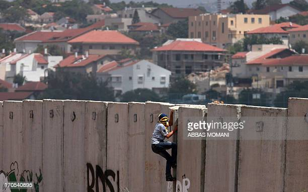 A Palestinian protester climbs Israel's controversial separation barrier during clashes with Israeli security forces following a demonstration...