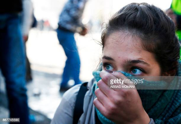 A Palestinian protester covers her face during clashes with Israeli troops following a protest against US President Donald Trump's decision to...