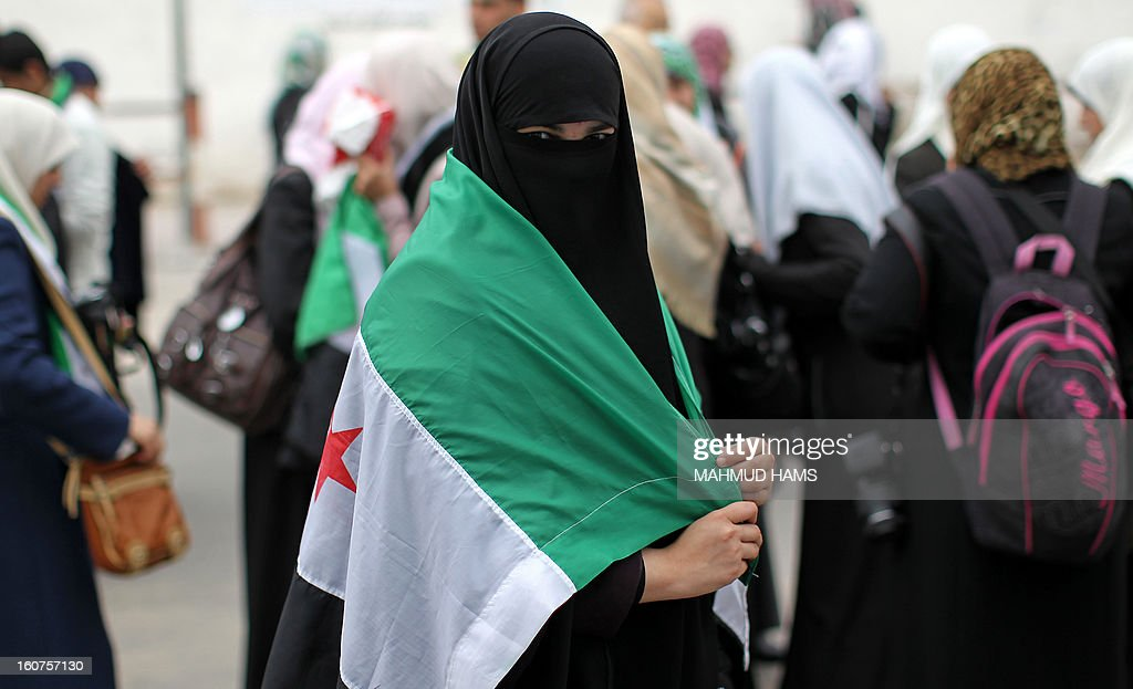 A Palestinian protester covers herself with a pre-Baath Syrian flag, now used by the Free Syrian Army, as she takes part in a demonstration in Gaza City in support of the Syrian people on February 5, 2013. Pressure mounted on Syrian President Bashar al-Assad to respond to a surprise offer of talks by his main political opponents aimed at ending warfare in which tens of thousands of people have died. AFP PHOTO / MAHMUD HAMS