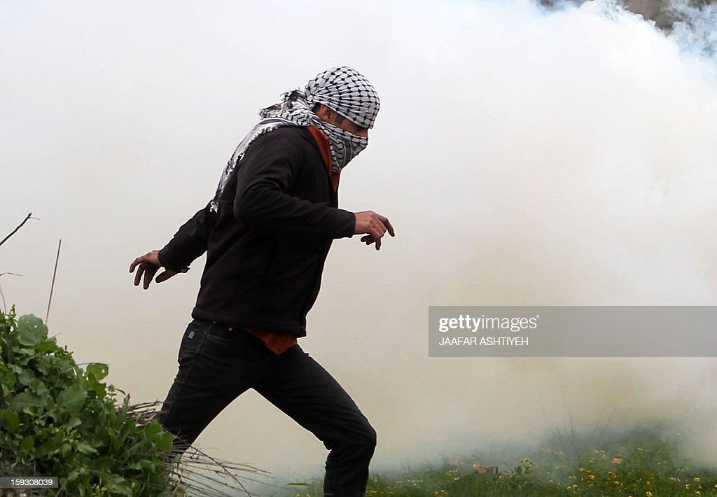 A Palestinian protester covers his face to protect himself from the smoke of tear gas during a protest against the expropriation of Palestinian land by Israel on January 11, 2013 in the village of Kafr Qaddum, near Nablus, in the occupied West Bank.