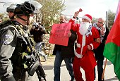 A Palestinian protester dressed in a Father Christmas costume argues with an Israeli border policeman during a demonstration against the Israeli...