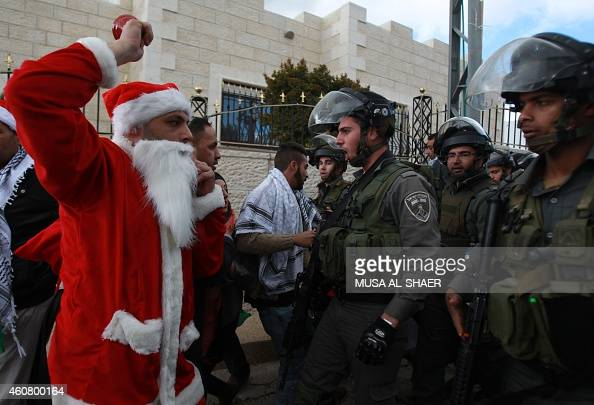 A Palestinian protester dressed in a Father Christmas costume argues with members of the Israeli security forces during a demonstration against the...