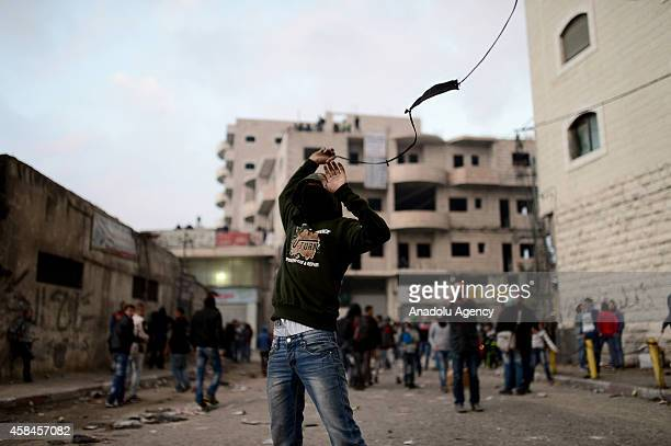 Palestinian protester fires a slingshot during the clashes with Israeli police at Shuafat refugee camp after a Palestinian rammed his vehicle into a...