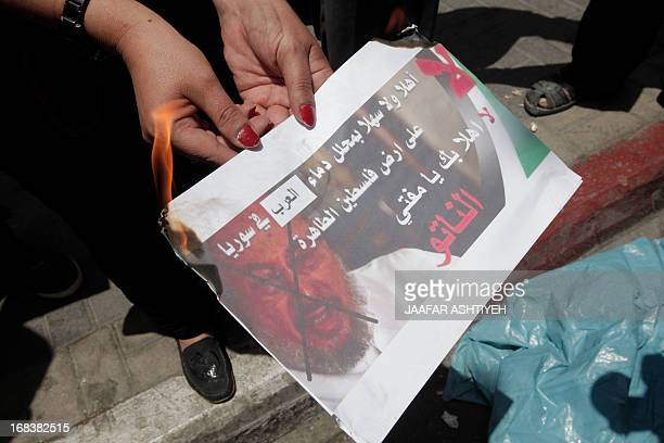 A Palestinian protester from the Popular Front for the Liberation of Palestine burns a poster featuring chairman of the International Union of Muslim...
