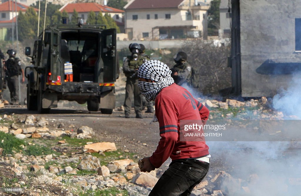 A Palestinian protester gathers stones to throw at Israeli soldiers during a demonstration against the expropriation of Palestinian land by Israel in the village of Kfar Qaddum, near the occupied West Bank city of Nablus, on January 4, 2013.