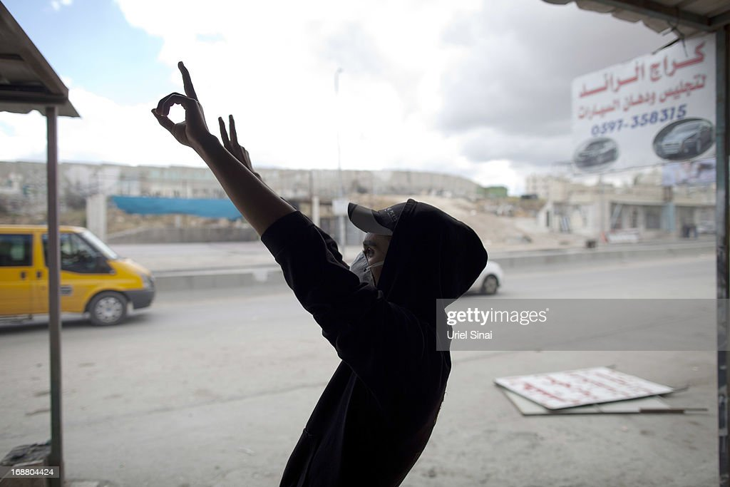 A Palestinian protester gestures during clashes with the Israeli army during Nakba day on May 15, 2013 near the Qalandia checkpoint at the outskirts of Ramallah, the West Bank. Palestinians mark Israel's establishment in 1948 with 'Nakba' or 'catastrophe' day on May 15, to remember the thousands of Palestinians who fled or were expelled during the creation of the Jewish state and the subsequent war.