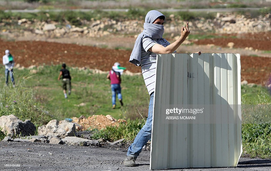 A Palestinian protester gestures obscenely at Israeli security forces (not seen) during clashes outside Ofer prison near the West Bank city of Ramallah on April 3, 2013 following a protest against the death of a Palestinian prisoner while in detention. Maisara Abu Hamdiyeh, who had served 10 years of a life sentence for attempted murder, died in an Israeli hospital two months after being diagnosed with throat cancer. The Palestinian leadership has accused Israel of medical negligence with news of his death sparking angry clashes.