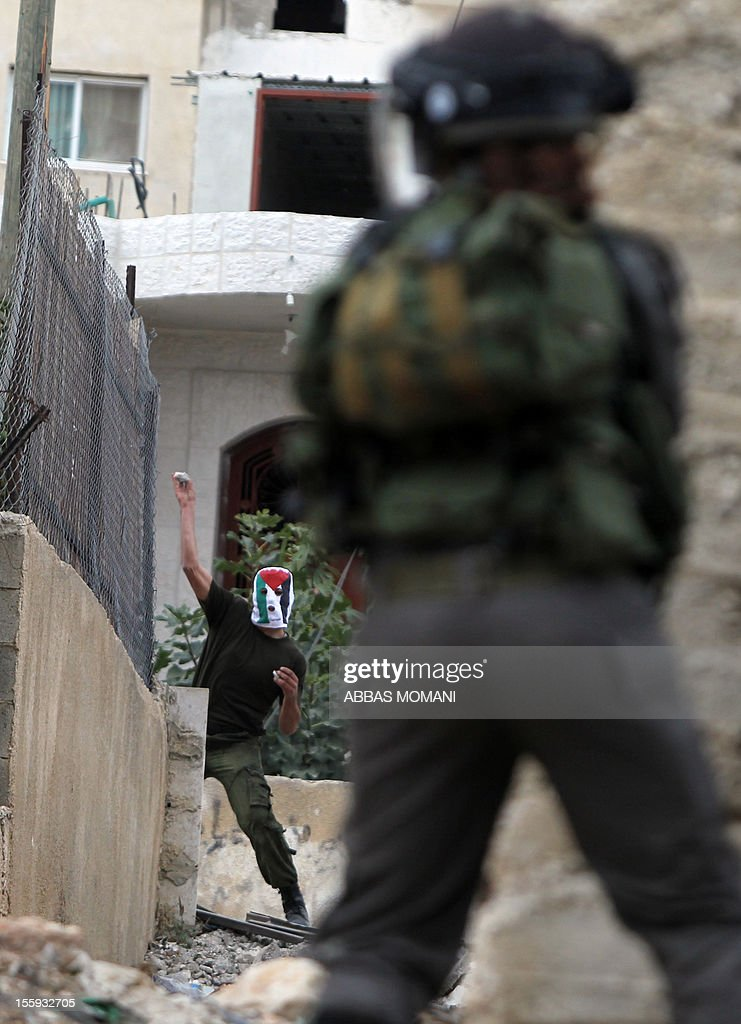 A Palestinian protester, hiding his face with a mask bearing the colours of the national flag, hurls stones at Israeli soldiers during a demonstration against the expropriation of Palestinian land by Israel in the West Bank village of Nabi Saleh near Ramallah, on November 9, 2012.