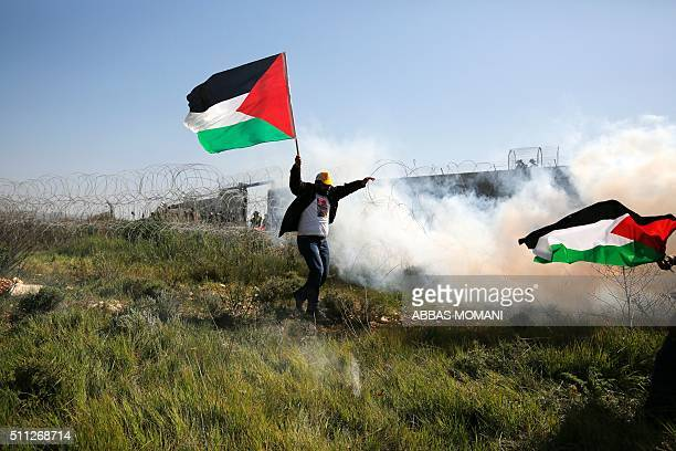 A Palestinian protester holding a national flag runs away from tear gas smoke during clashes with Israeli security forces following a march on...