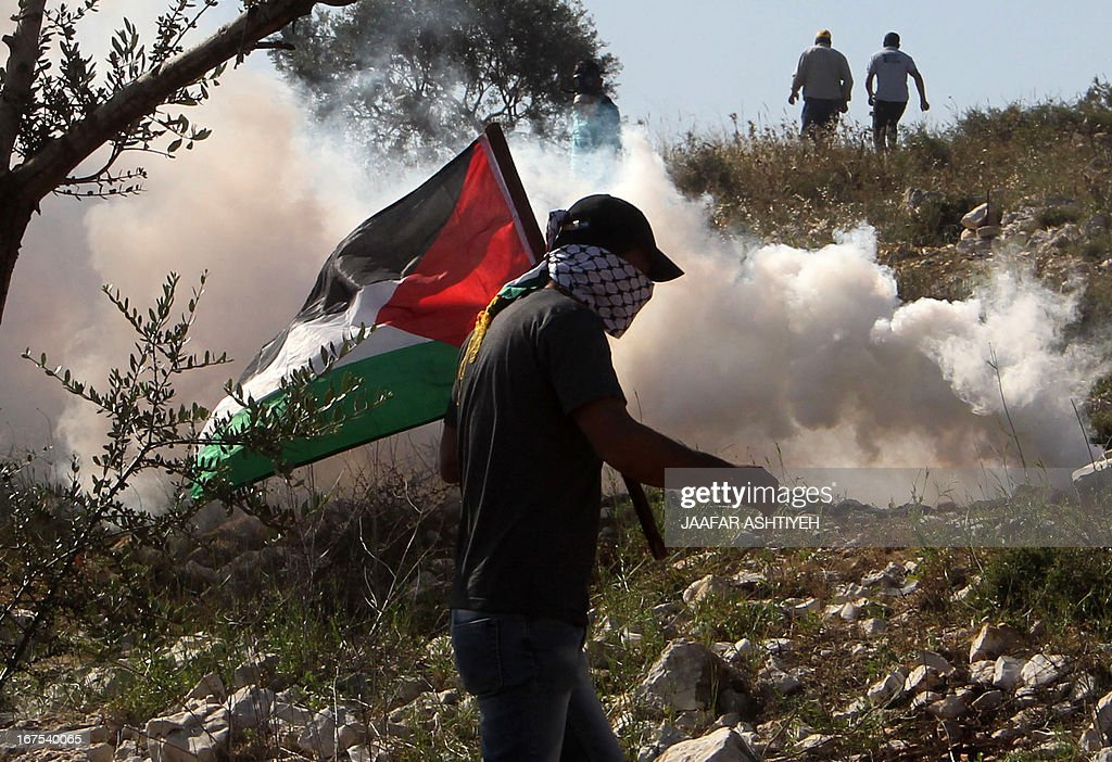 A Palestinian protester holding his national flag runs away from a tear gas canister fired by Israeli security forces during clashes following a demonstration against the expropriation of Palestinian land by Israel in the village of Kfar Qaddum, near Nablus in the occupied West Bank on April 26, 2013. AFP PHOTO / JAAFAR ASHTIYEH