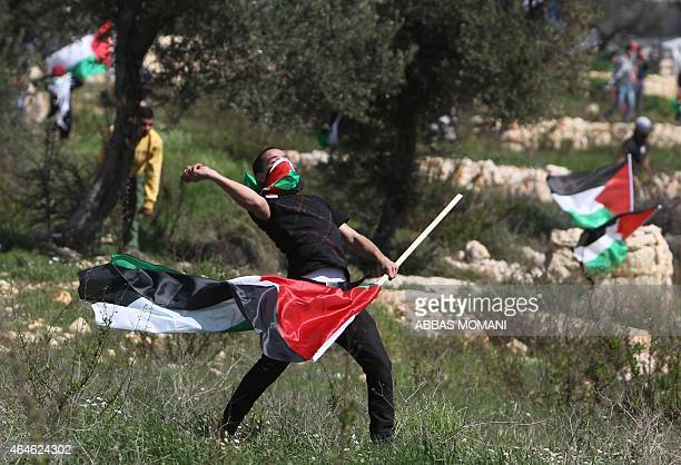 A Palestinian protester holding his national flag throws rocks during clashes with Israeli security forces on February 27 2015 following a...