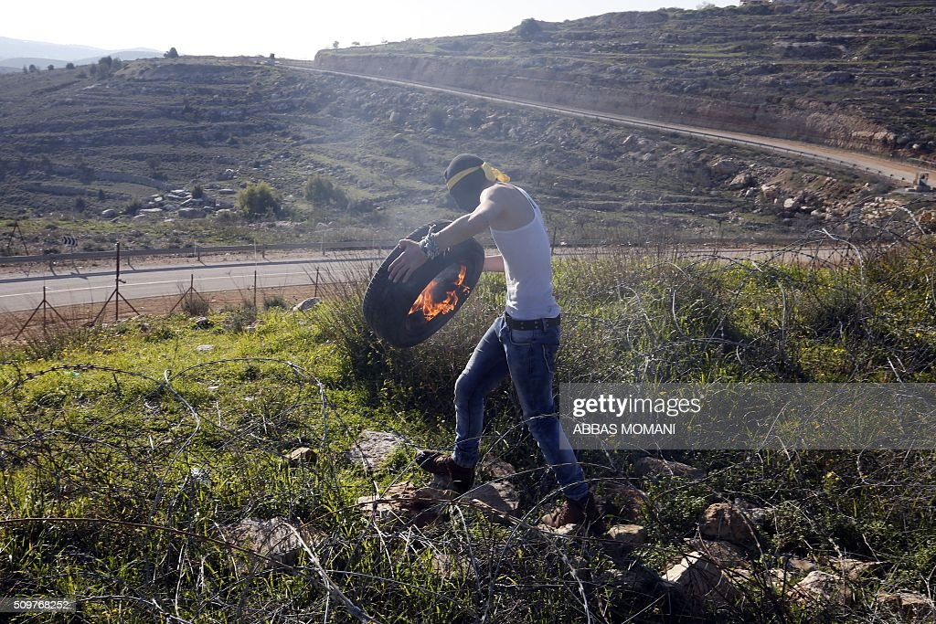 A Palestinian protester holds a burning tyre past barbed wire during clashes with Israeli troops following a protest on February 12, 2016 in solidarity with Palestinian prisoners held in Israeli jails, outside the compound of the Israeli-run Ofer Prison near Betunia in the occoupied West Bank. / AFP / ABBAS MOMANI