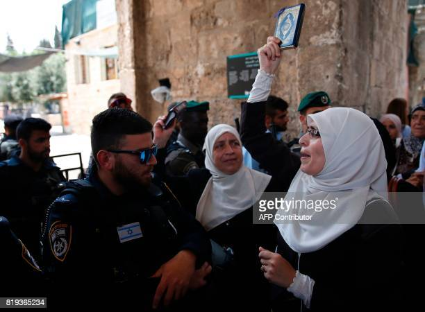 Palestinian protester holds a copy of the Koran Islam's holy book and shouts slogans in front of Israeli security forces during a demonstration in...